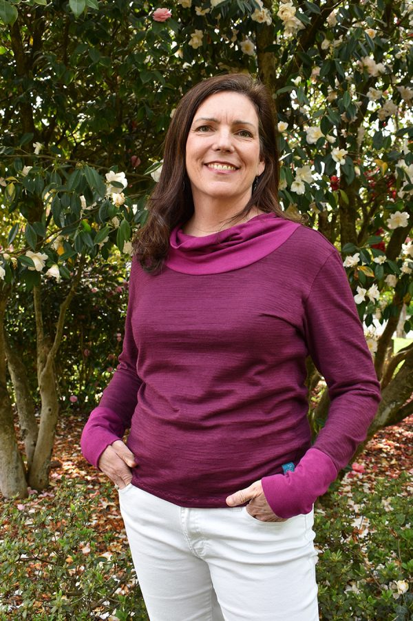 smiling lady wearing a long sleeve cowl neck top in huckelberry and fuchsia with white pants and a blooming camelia bush in the background.