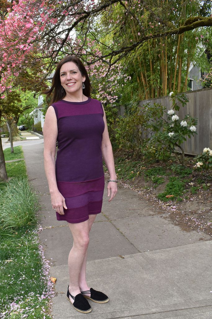 Caryl in a 60s style sleeveless purple hemp dress on a walk under blooming pink trees.