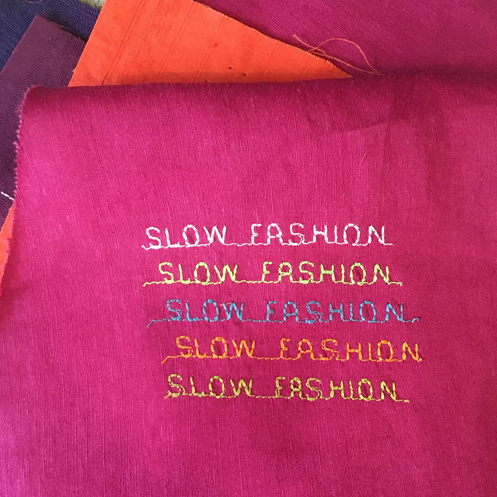 SLOW FASHION stitched in block letters 5 times on bright fuchsia fabric