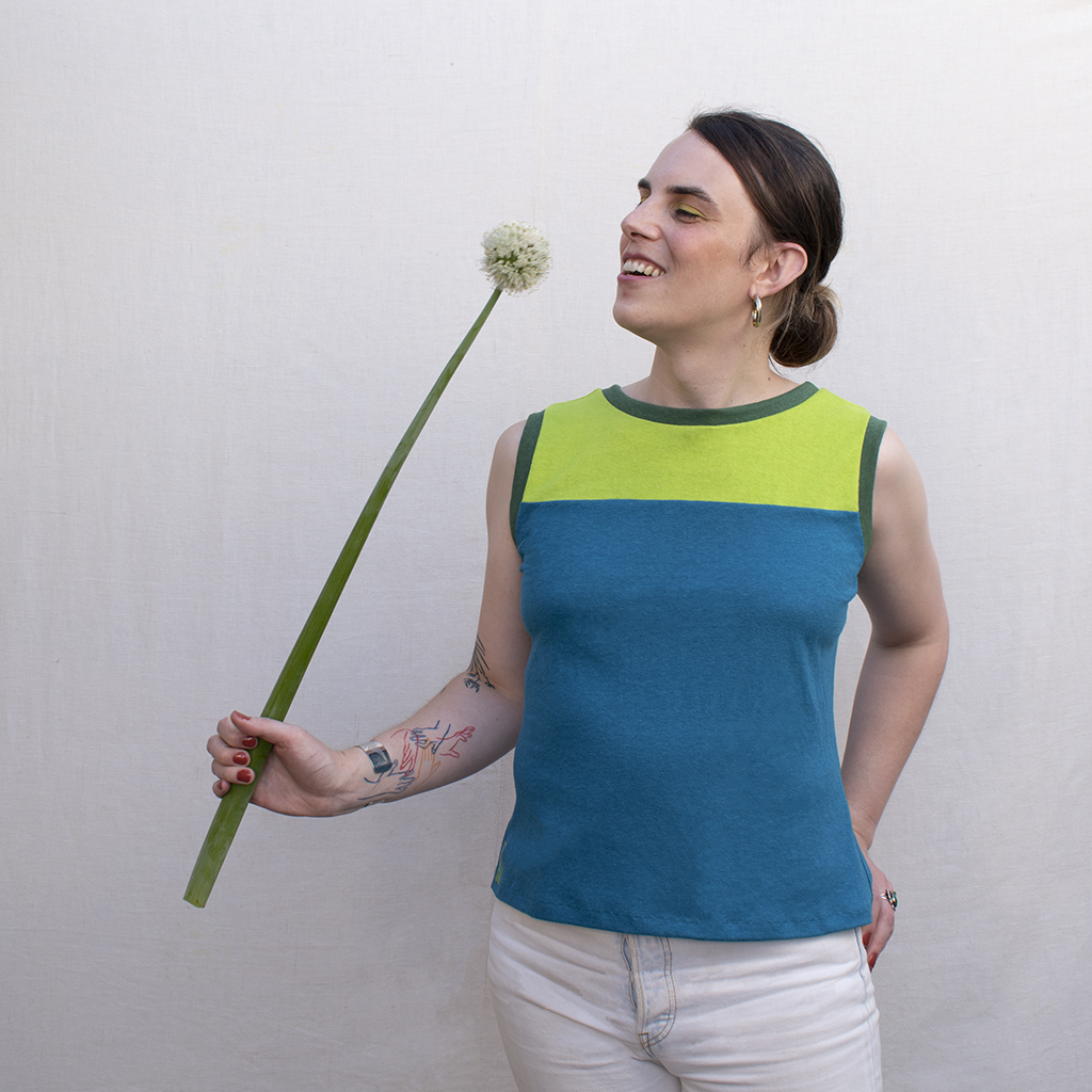 trans gender model in lime green and turquoise tank top looking at a giant allium flower
